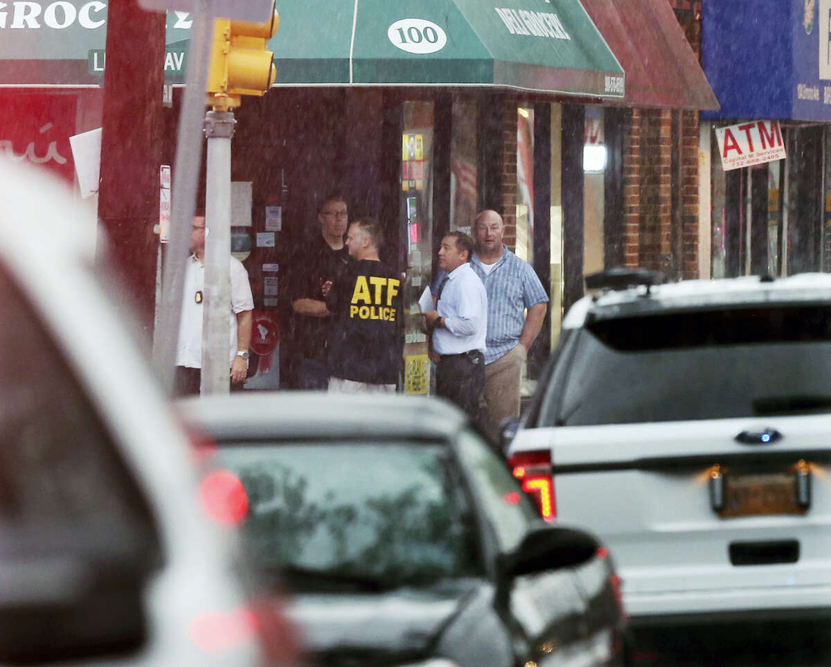 Police and officials gather in the doorway of a building early Sept. 19, 2016 in Elizabeth, N.J. A suspicious device found in a trash can near a train station exploded early Monday as a bomb squad was attempting to disarm it with a robot, officials said.