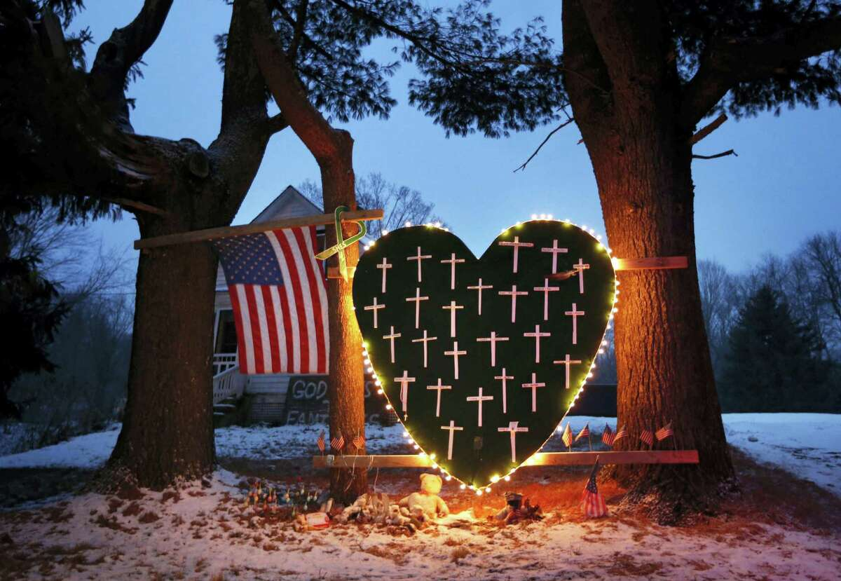 In this Dec. 14, 2013 file photo, a makeshift memorial with crosses for the victims of the Sandy Hook Elementary School shooting massacre stands outside a home in Newtown on the one-year anniversary of the shootings. With sweeping views of Newtown's rolling hills, a field at the town's highest point emerged early on as the first choice for planners of a permanent memorial to honor the 26 people killed at Sandy Hook Elementary School. Open space advocates, however, objected to construction on the pristine area known as the High Meadow. As more community members have spoken out, the planning commission, which includes parents of the some of the massacre victims, agreed recently to go back and consider other options.