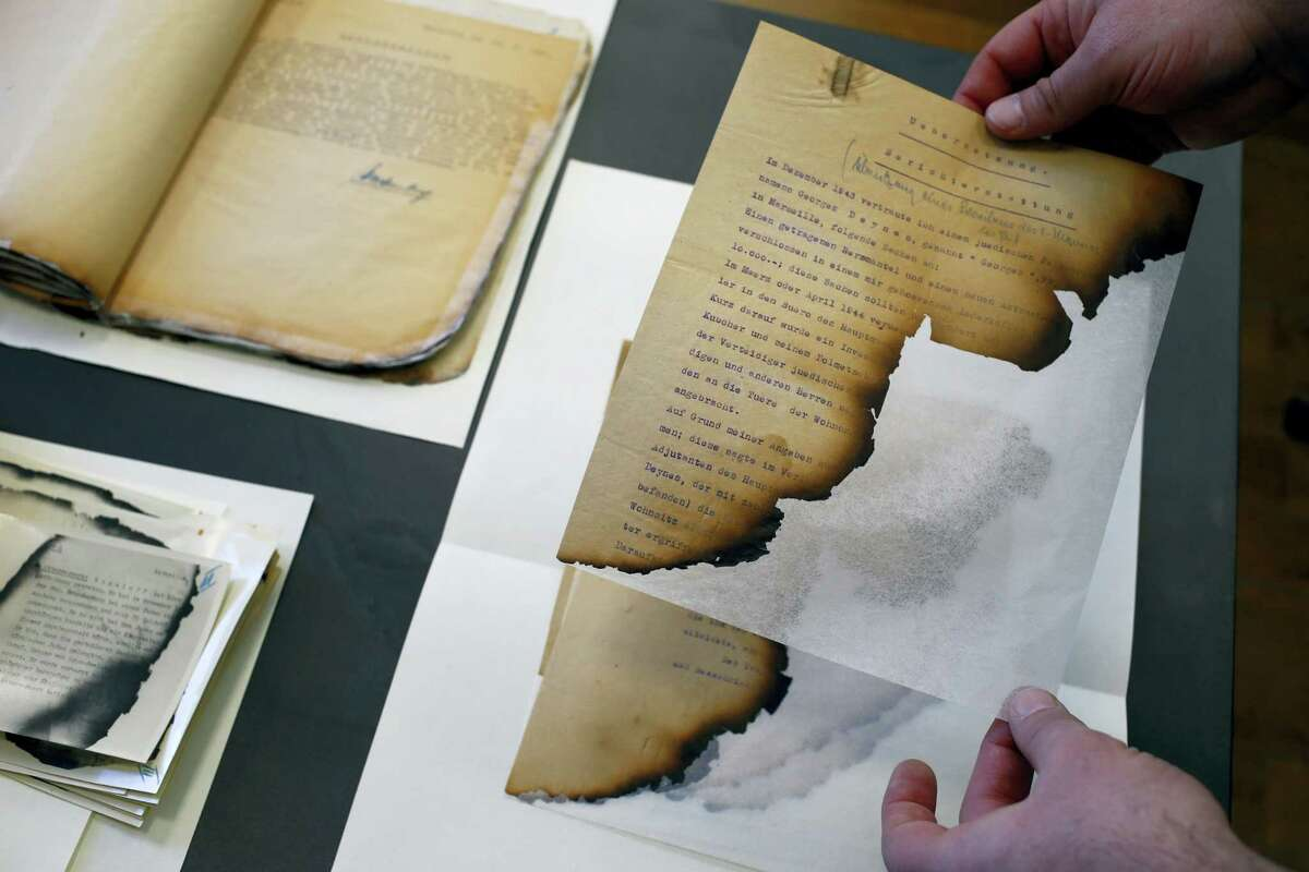 The files of the Gestapo (the Nazi secret police), partially burnt in a blaze in Marseille, and stored for years in the archives rooms of the medieval castle of Vincennes, are displayed in Vincennes, east of Paris, Wednesday, March 16, 2016. A team of French historians unveiled Wednesday some secret services' archives from WWII, letters, reports, cables and photos from the rival intelligence agencies of the French Resistance, the collaborationist Vichy regime and the Nazi German authorities.