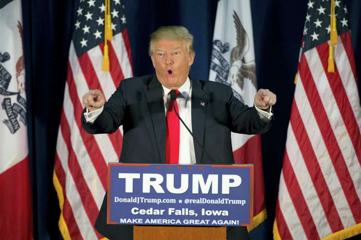 Republican presidential candidate Donald Trump points to the crowd while speaking at a rally Tuesday in Cedar Falls, Iowa.