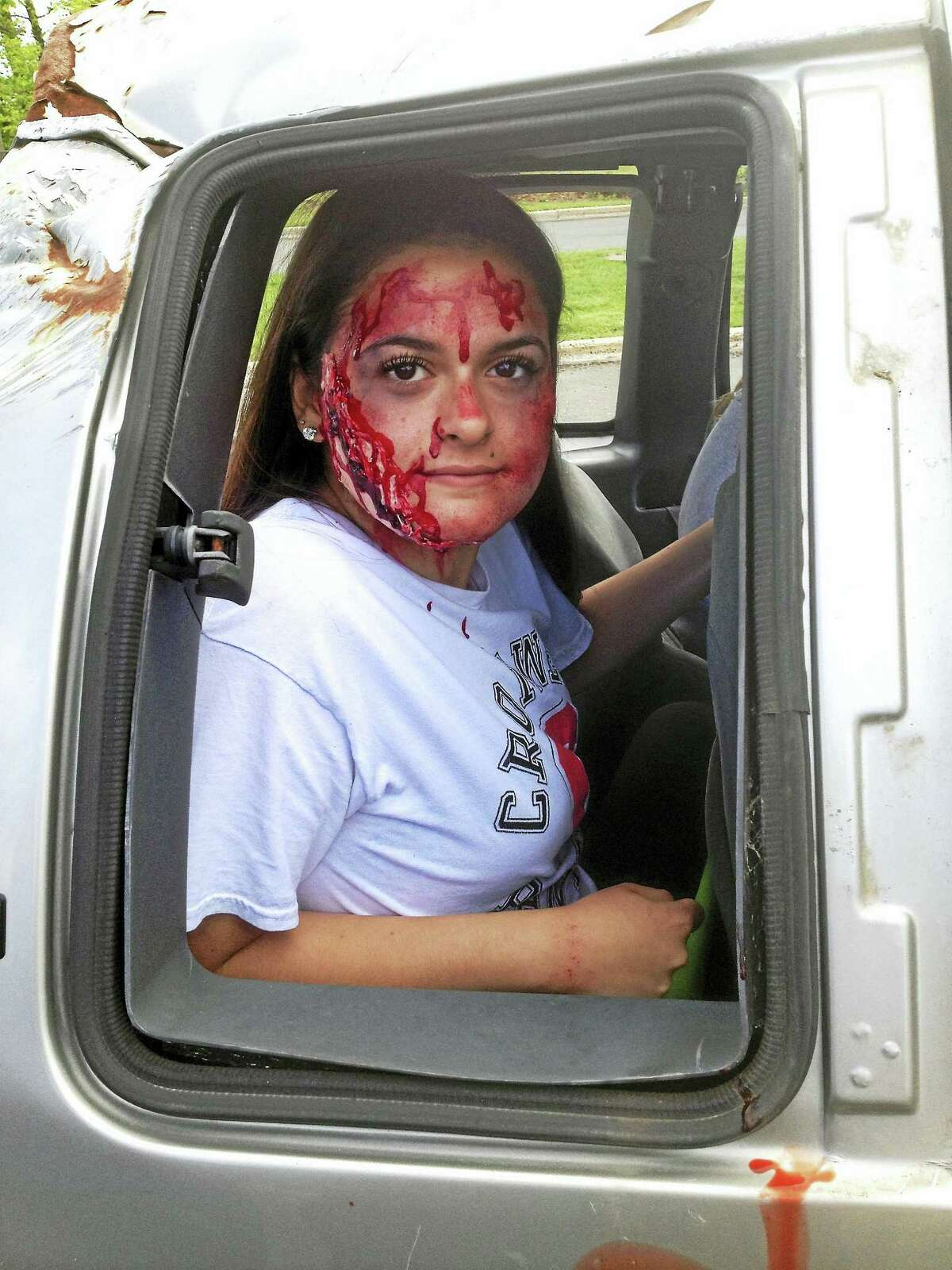 """Cromwell High School students participated in a mock crash to simulate what happens when someone drives while under the influence of drugs or alcohol. Here a participant plays her part in the """"accident."""""""