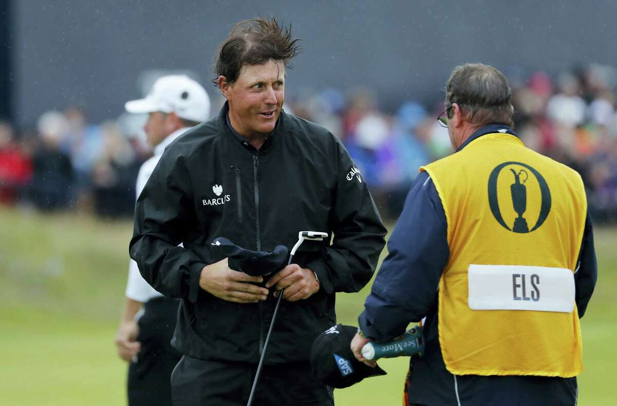 Phil Mickelson shakes hands with Ricci Roberts, the caddie for Ernie Els, on the 18th green on Friday.