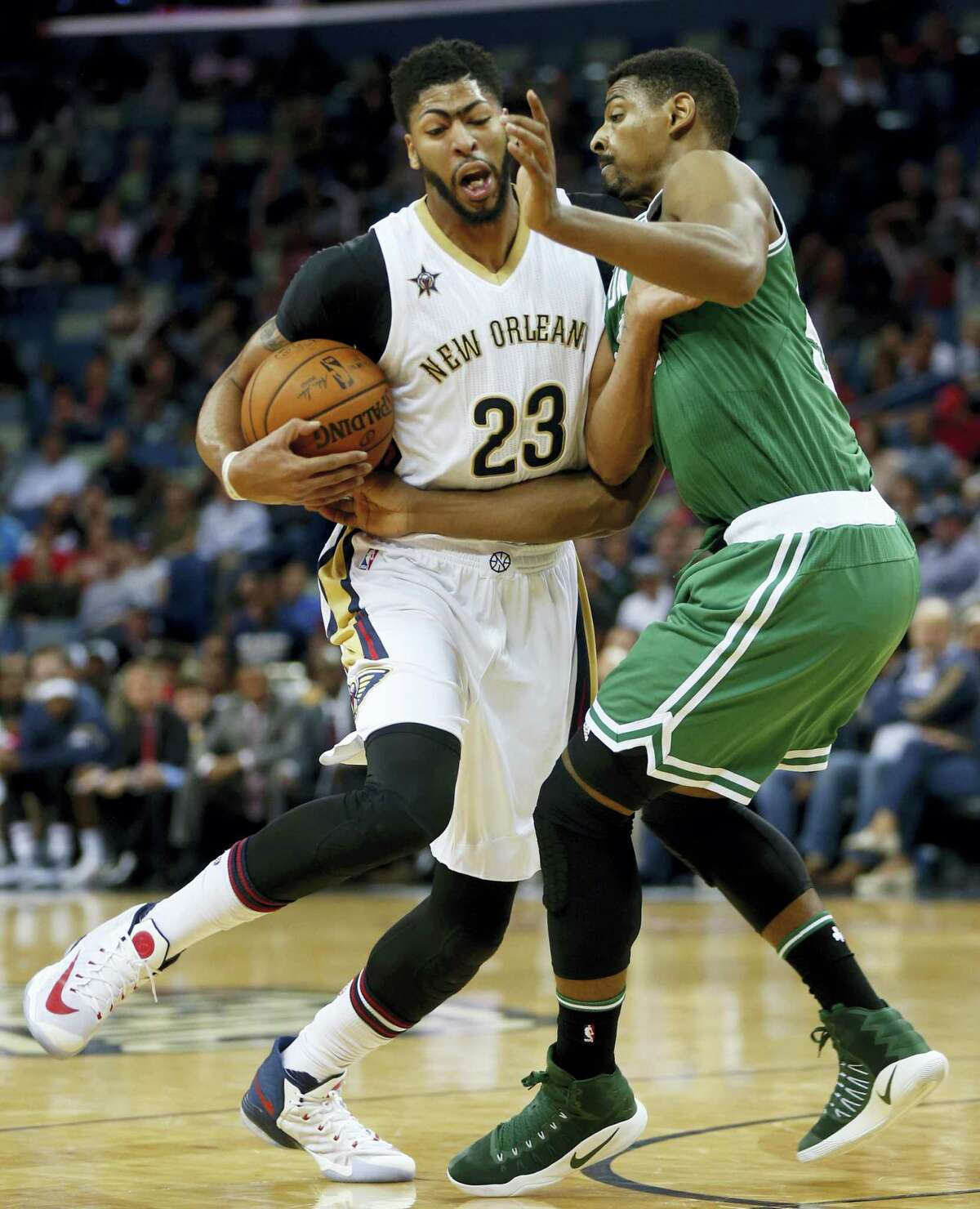 New Orleans Pelicans forward Anthony Davis (23) drives the lane against Boston Celtics forward Jordan Mickey in the first half of an NBA basketball game in New Orleans on Nov. 14, 2016.