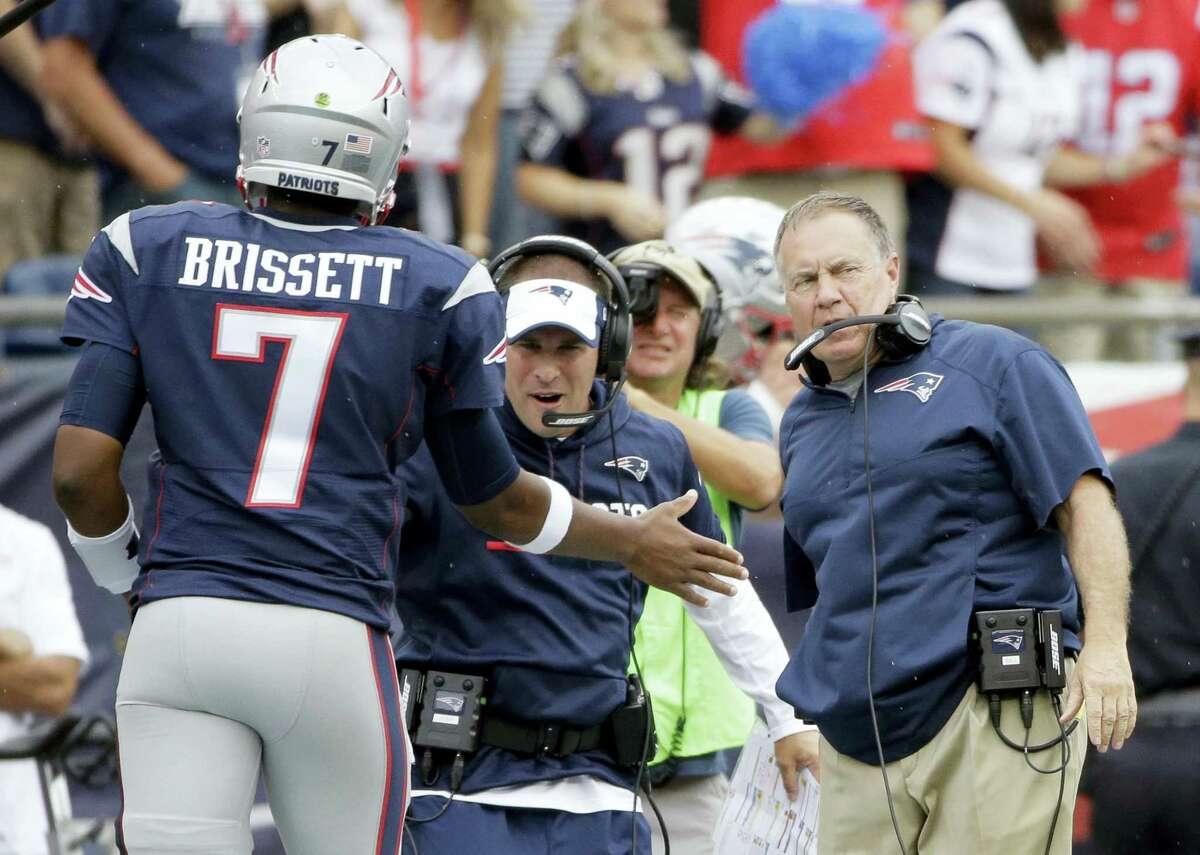 Patriots offensive coordinator Josh McDaniels, center, alongside head coach Bill Belichick, right, congratulate quarterback Jacoby Brissett (7) after LeGarrette Blount's touchdown run during the second half Sunday.