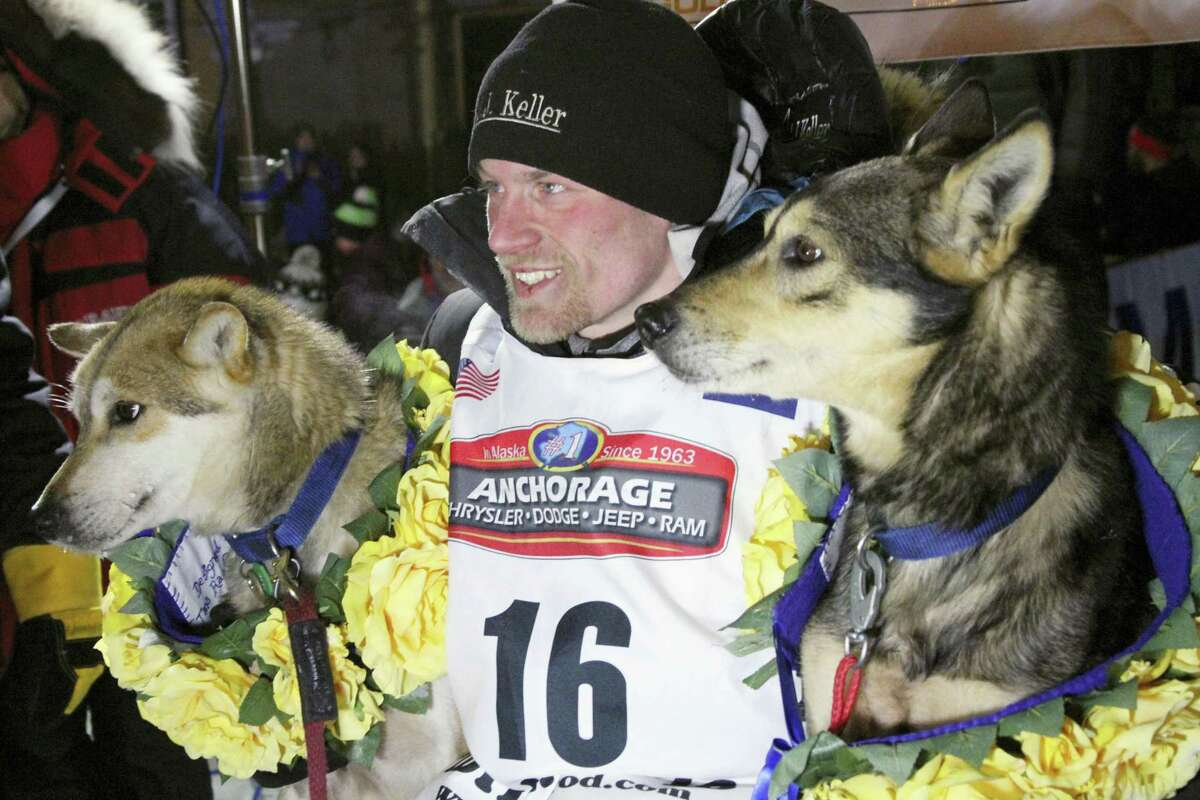 Dallas Seavey poses with his lead dogs Reef, left, and Tide after winning the Iditarod on Tuesday.