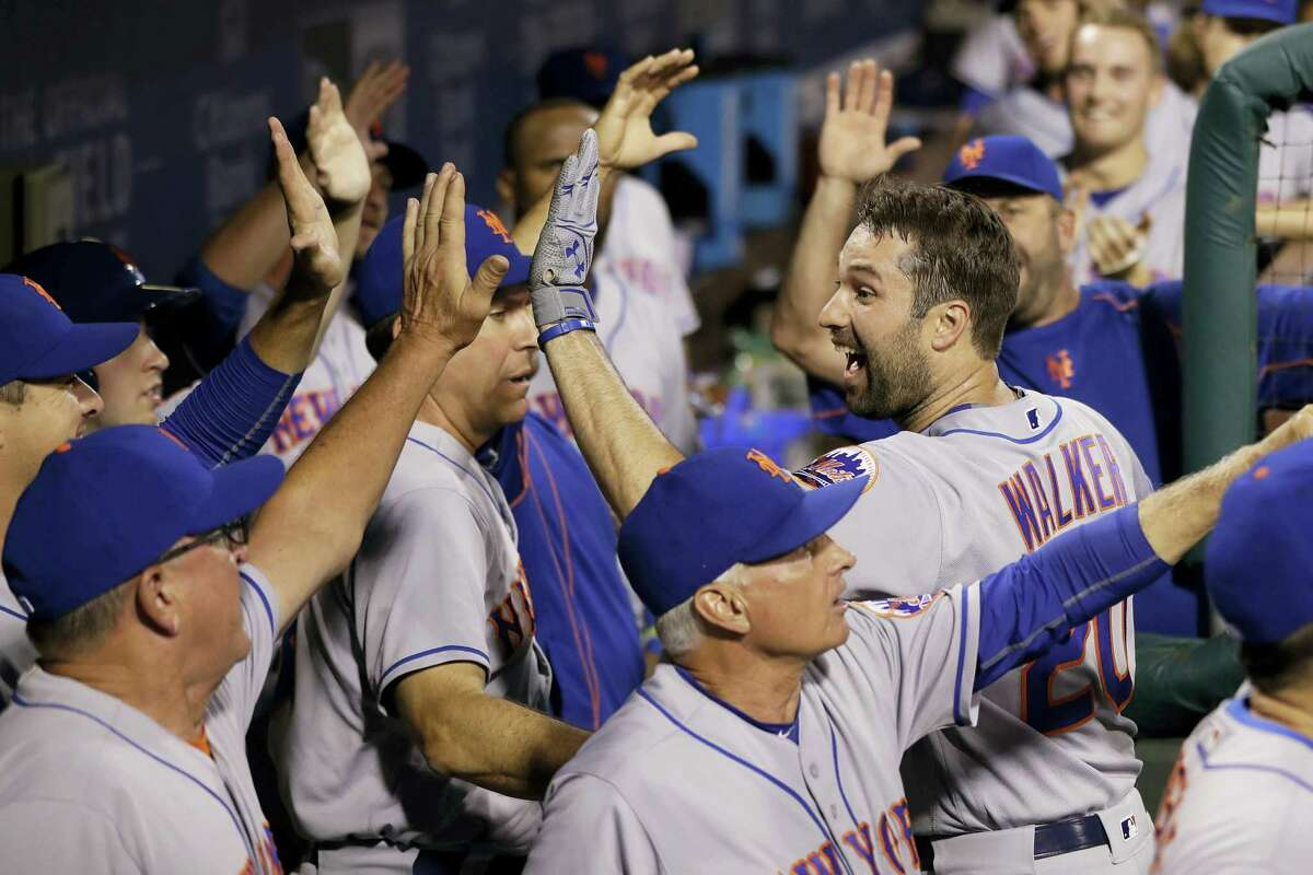 Neil Walker, right, celebrates with teammates after hitting a three-run home run during the sixth inning on Friday.