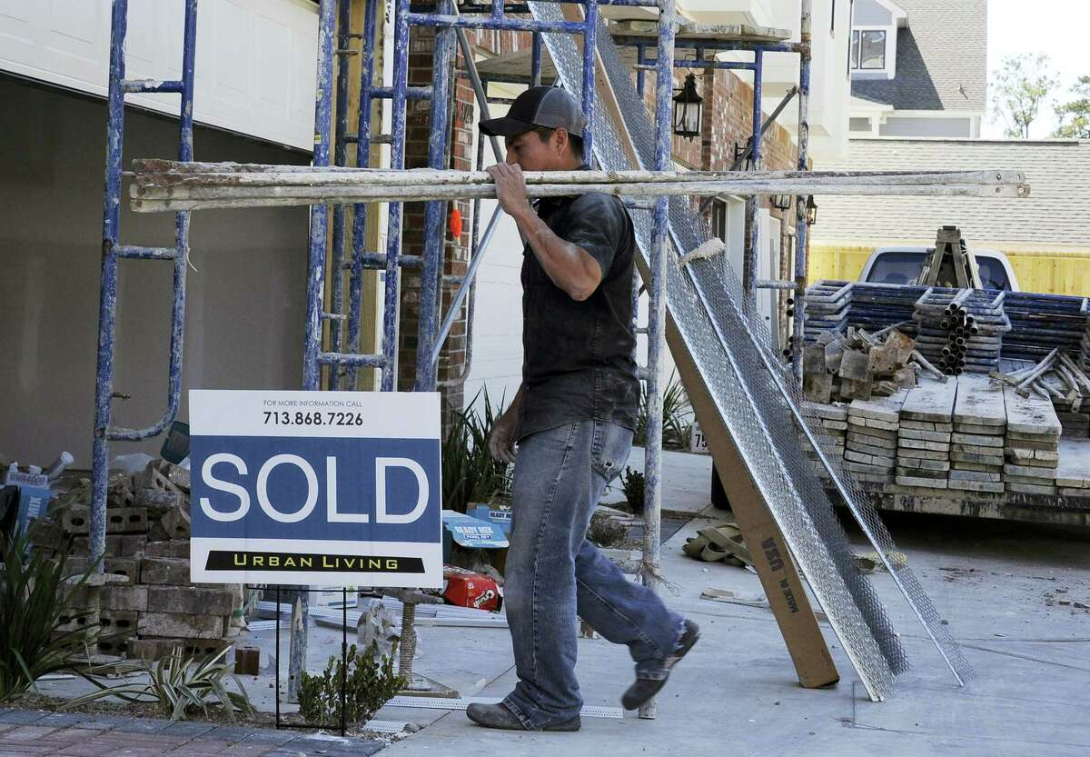 """In this Feb. 16, 2016 photo, a worker walks past a """"Sold"""" sign at a construction site of new townhouses, in Houston. On May 17, 2016 the Commerce Department reports on U.S. home construction in April."""