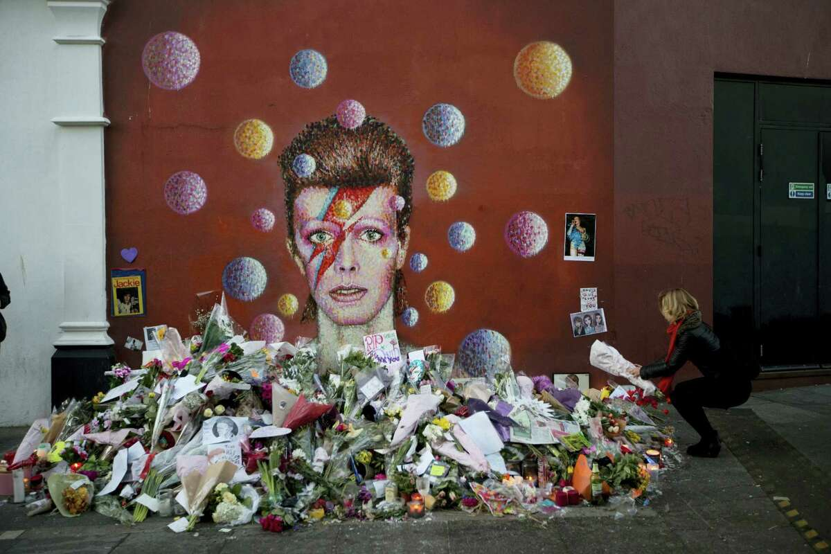 A woman lays flowers beside a mural of British singer David Bowie by artist Jimmy C in Brixton, south London, Tuesday, Jan. 12, 2016. Bowie, the other-worldly musician who broke pop and rock boundaries with his creative musicianship, nonconformity, striking visuals and a genre-spanning persona he christened Ziggy Stardust, died of cancer Sunday aged 69. He was born in Brixton.