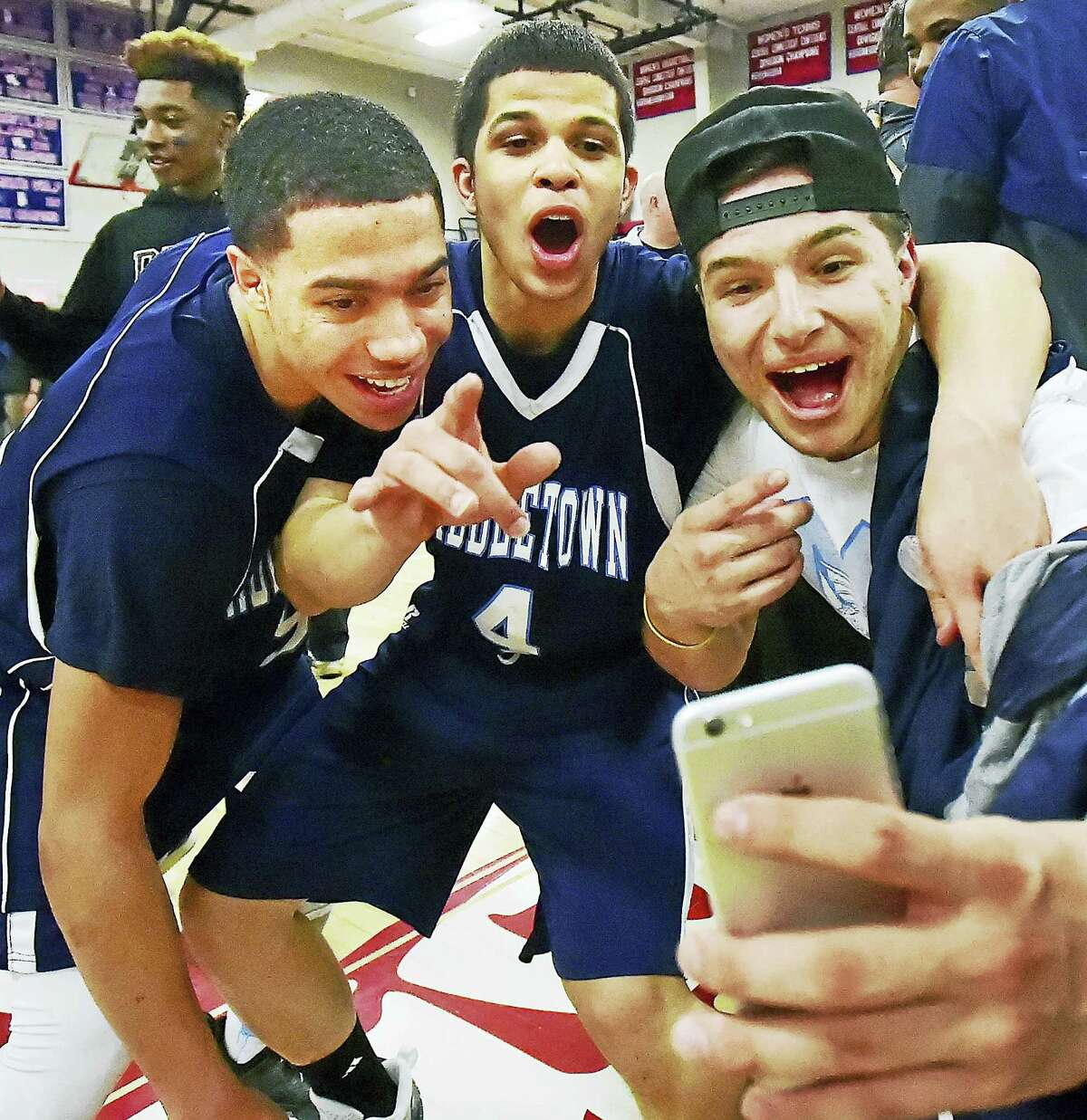 Middletown seniors Caylen Williams and Emmitt Riddick take a selfie with their classmate Josh Tow after Tuesday's 73-68 win over Newington in a Class L semifinal game in Berlin.