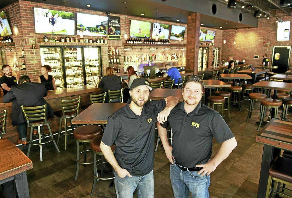 (Peter Hvizdak - New Haven Register)Manager Troy Livingston, left, and market development partner Matt Christy of the World of Beer pub in the Connecticut Post Mall in Milford Wednesday, May 11, 2016. The World of Beer has 63 beers on tap and at over 500 different styles and brands of beer in bottles and cans.