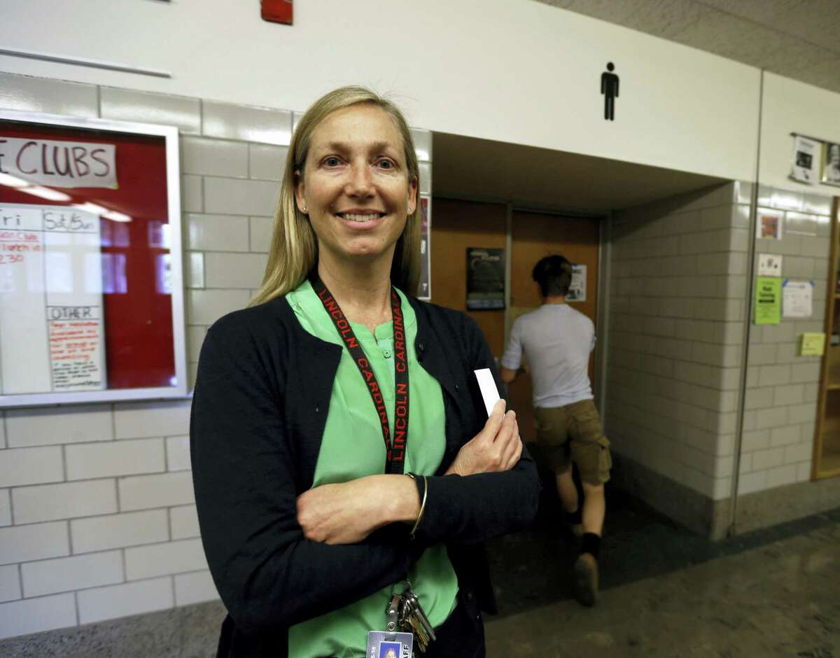 """In this photo taken May 13, 2016, Lincoln High School principal Peyton Chapman poses for a photo in the halls of the school in Portland, Ore. on May 13, 2016. Chapman recalls the """"challenging times"""" about seven years when a transgender student who identified as female transferred there after being bullied at her previous school."""