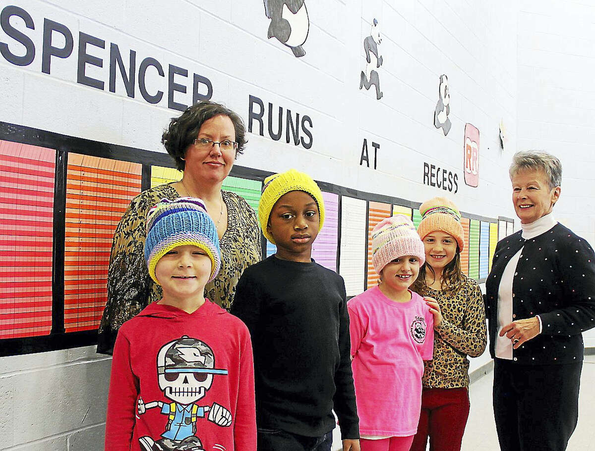 Spencer School students, from left, Devin Morris, Isaiah Anderson, Olivia Roy and Gianna Salafia wear new hats presented by Sarah Duda, rear, and Donna Duda, far right, who crocheted 300, one for every child in her granddaughter's school.