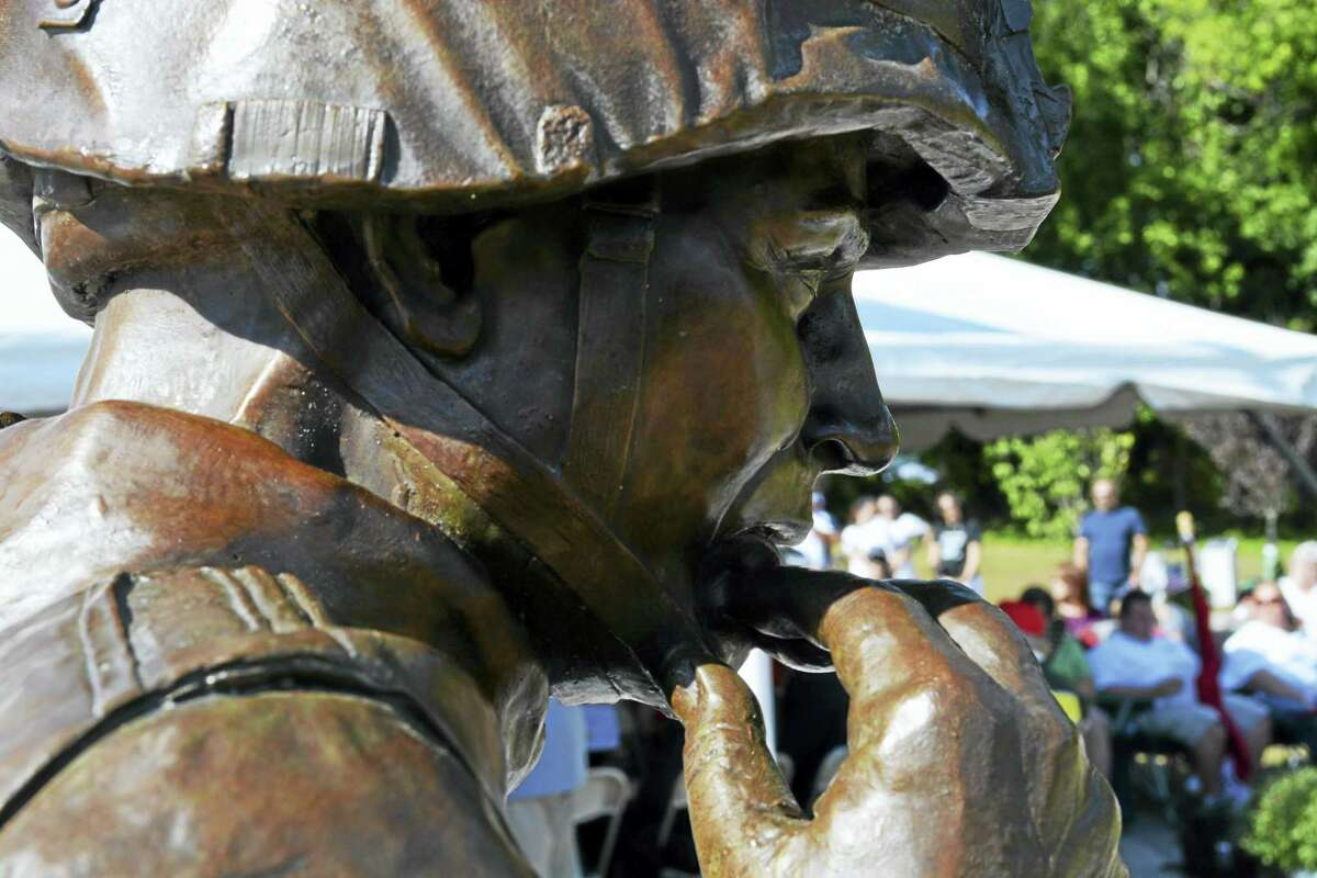 """The bronze statue, """"First Tear,"""" is at the center of the memorial. The work of sculptor Andrew Chernak of Pennsylvania depicts a soldier with tears streaming from his eyes, comforting a dead comrade whose head he cradles."""