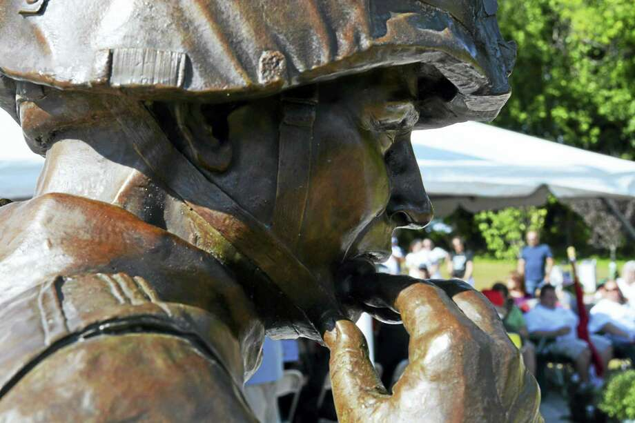 """The bronze statue, """"First Tear,"""" is at the center of the memorial. The work of <a href=""""http://www.andrewchernak.com/"""">sculptor Andrew Chernak of Pennsylvania</a> depicts a soldier with tears streaming from his eyes, comforting a dead comrade whose head he cradles. Photo: Cassandra Day — The Middletown Press"""