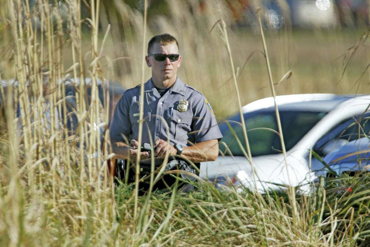 An Oklahoma City police officer looks through tall grass at a checkpoint at Will Rogers World Airport, Tuesday, Nov. 15 2016, in Oklahoma City. The airport was put on lockdown after a shooting at the main terminal.