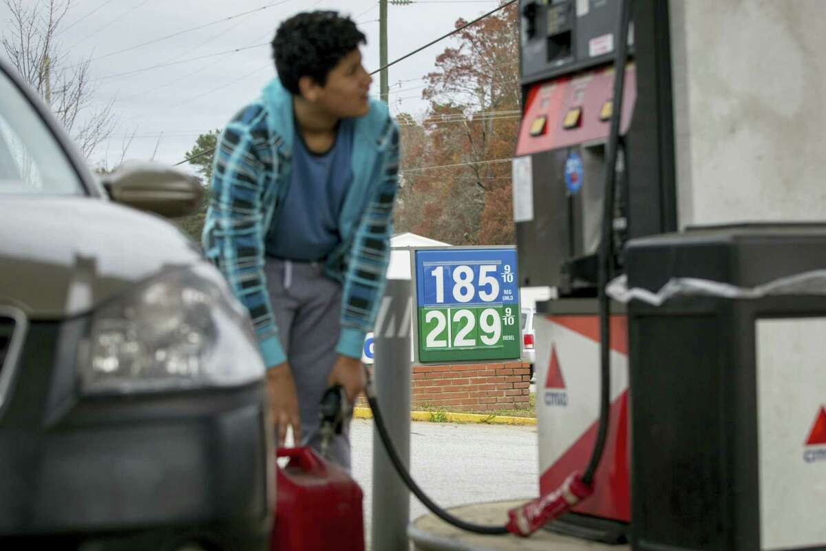 In this Wednesday, Nov. 25, 2015, photo, Cornelio Bonilla pumps gas at Best Food Mart gas station in Gainesville Ga. The price of oil continues to fall, extending a slide that has already gone further and lasted longer than most thought, and probing depths not seen since 2003.