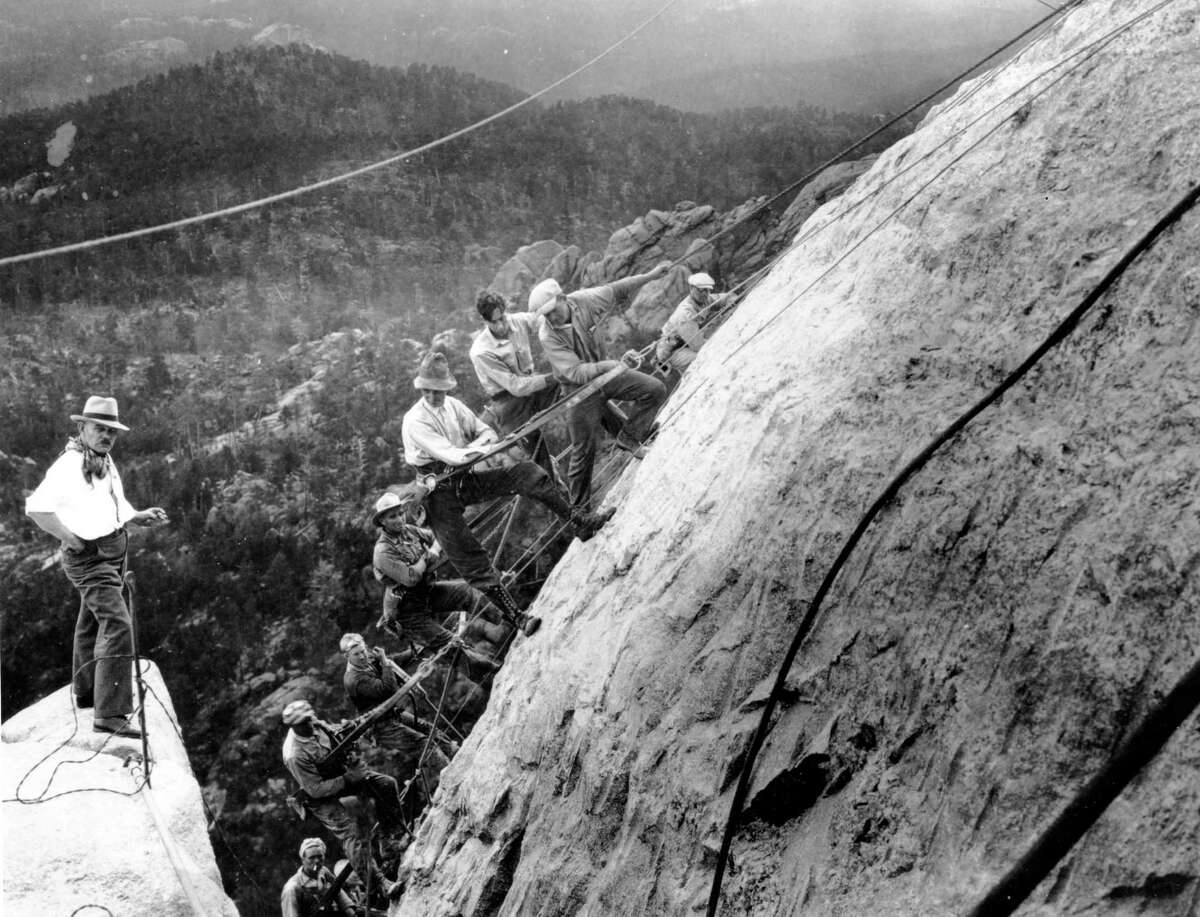 In this July, 22, 1929 photo, sculptor Gutzon Borglum, at left, directs drillers suspended by cables from the top of the mountain as they work on the head of President George Washington at the Mount Rushmore Memorial in the Black Hills area near Keystone, S.D. In October 2016, the memorial that through the years has become the state's most famous attraction and draws about 3 million visitors a year will mark 75 years since it was completed.