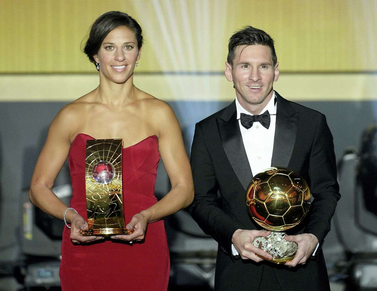 Carli Lloyd, left, and Lionel Messi pose with their trophies after winning the FIFA soccer player of the year awards on Monday.