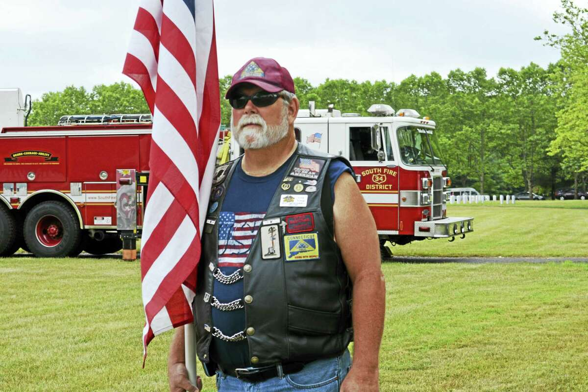 """At the Connecticut State Veterans Cemetery Middletown, a 3,000-niche columbarium was unveiled Thursday in a military ceremony which included the playing of """"Taps,"""" a color guard and a bagpiper player. Here, Greg Young of the Connecticut Patriot Guard Riders stands at attention during the proceedings."""