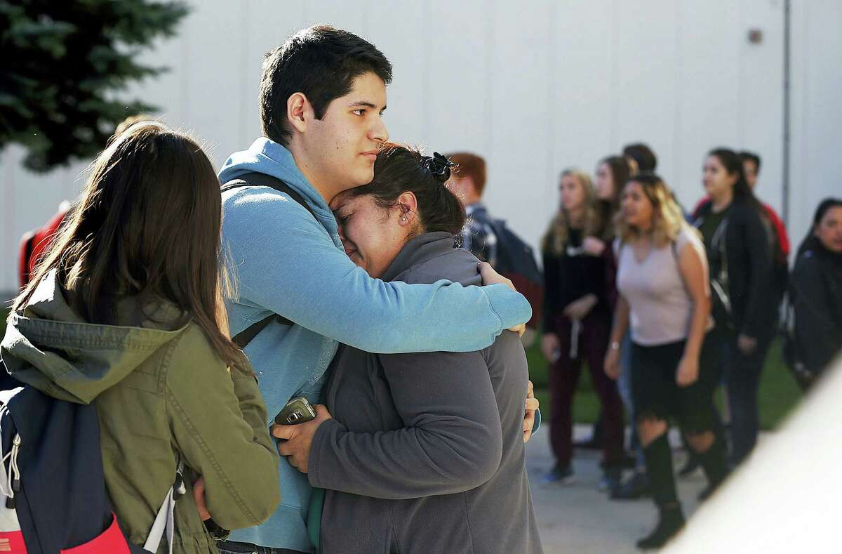 A family hugs as they reunite outside Mountain View High School in Orem, Utah on Tuesday, Nov. 15, 2016, following stabbings at the school.