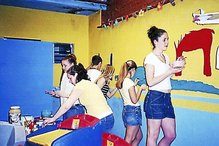 A group of Coginchaug Regional High School students paint the mural at its center in Oaxaca. Photo: Courtesy Marilyn Horn