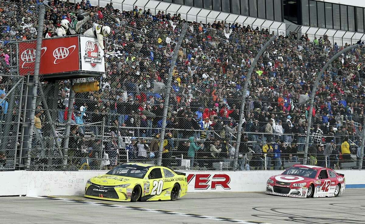 Matt Kenseth (20) takes the checkered flag ahead of Kyle Larson (42) to win Sunday at Dover International Speedway.