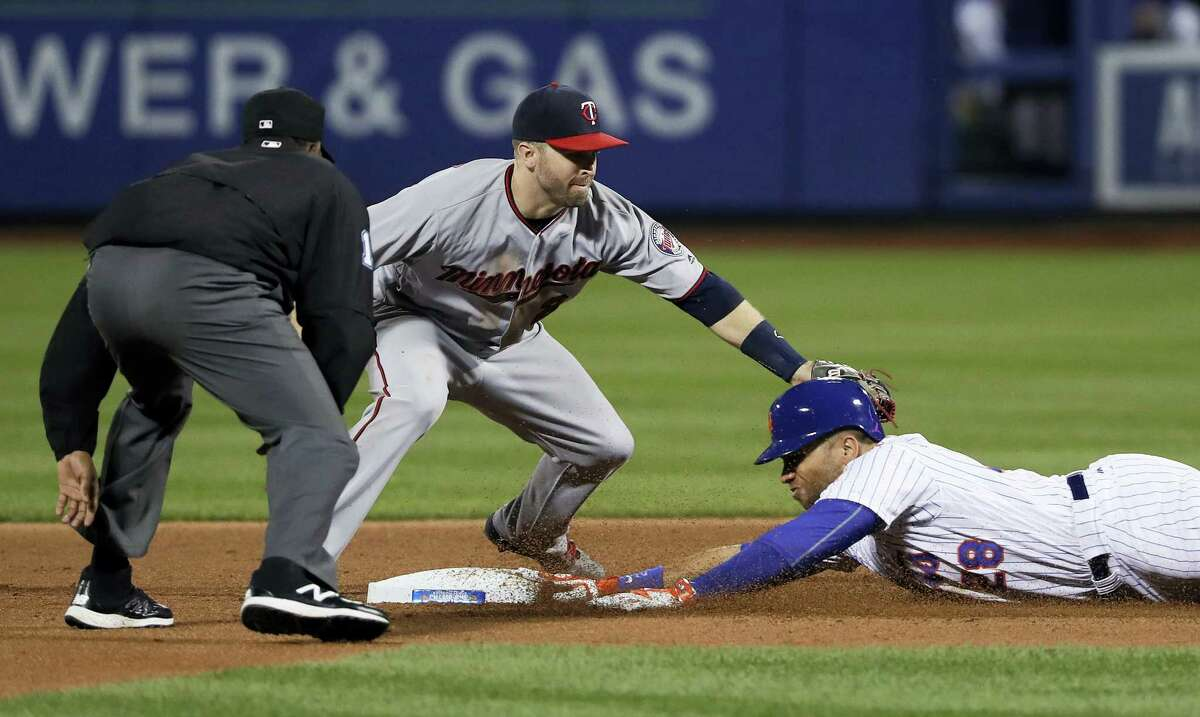 New York Mets' James Loney slides safely into second base ahead of the tag from Minnesota Twins second baseman Brian Dozier during the sixth inning Friday. Loney stretched a hit to right field into a double.