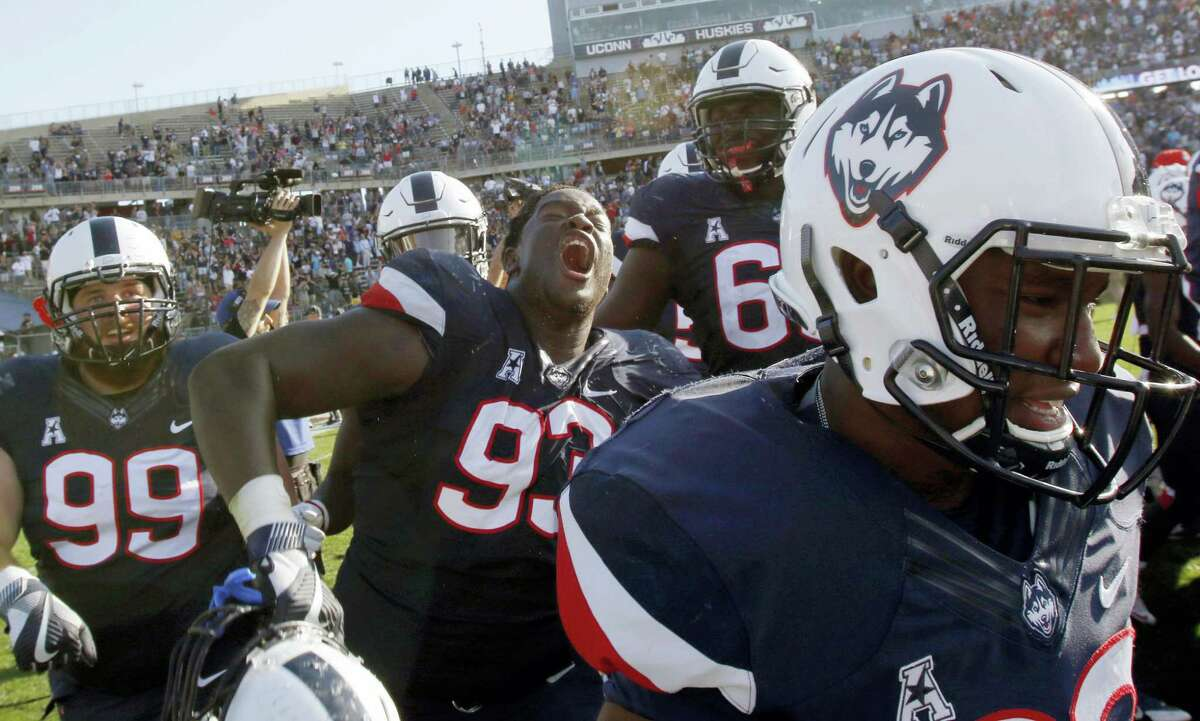 UConn's Folorunso Fatukasi, center, and teammates celebrate their 13-10 win over Virginia Saturday at Rentschler Field.