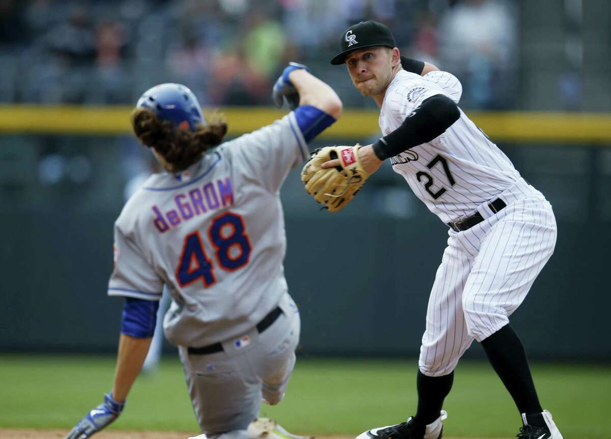 Colorado Rockies shortstop Trevor Story, throws to first base after forcing out Jacob deGrom at second base in the seventh inning on Sunday.