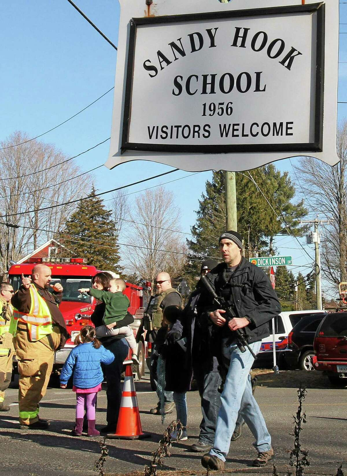 Parents walk past police and firefighters away from the Sandy Hook Elementary School with their children following a shooting at the school, Friday, Dec. 14, 2012 in Newtown.