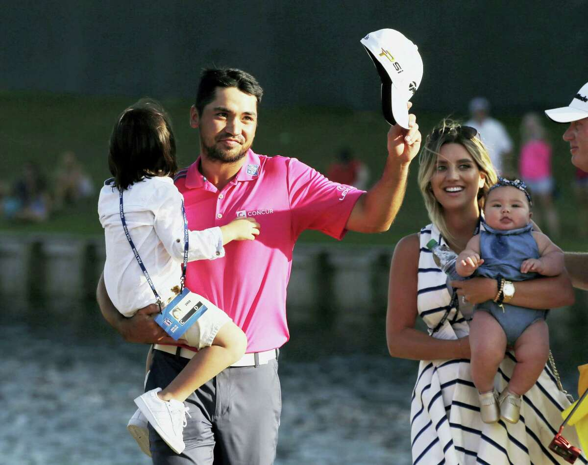 Jason Day tips his hat as he walks off the 18th green with his family after winning The Players Championship Sunday in Ponte Vedra Beach, Fla.