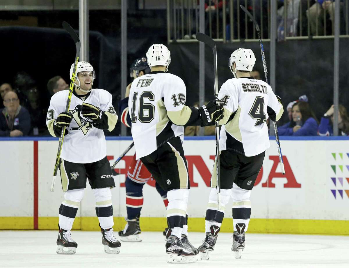 Pittsburgh Penguins defenseman Justin Schultz (4) is congratulated by teammates Eric Fehr (16) and Conor Sheary (43) after scoring a goal against the New York Rangers in the second period Sunday in New York.