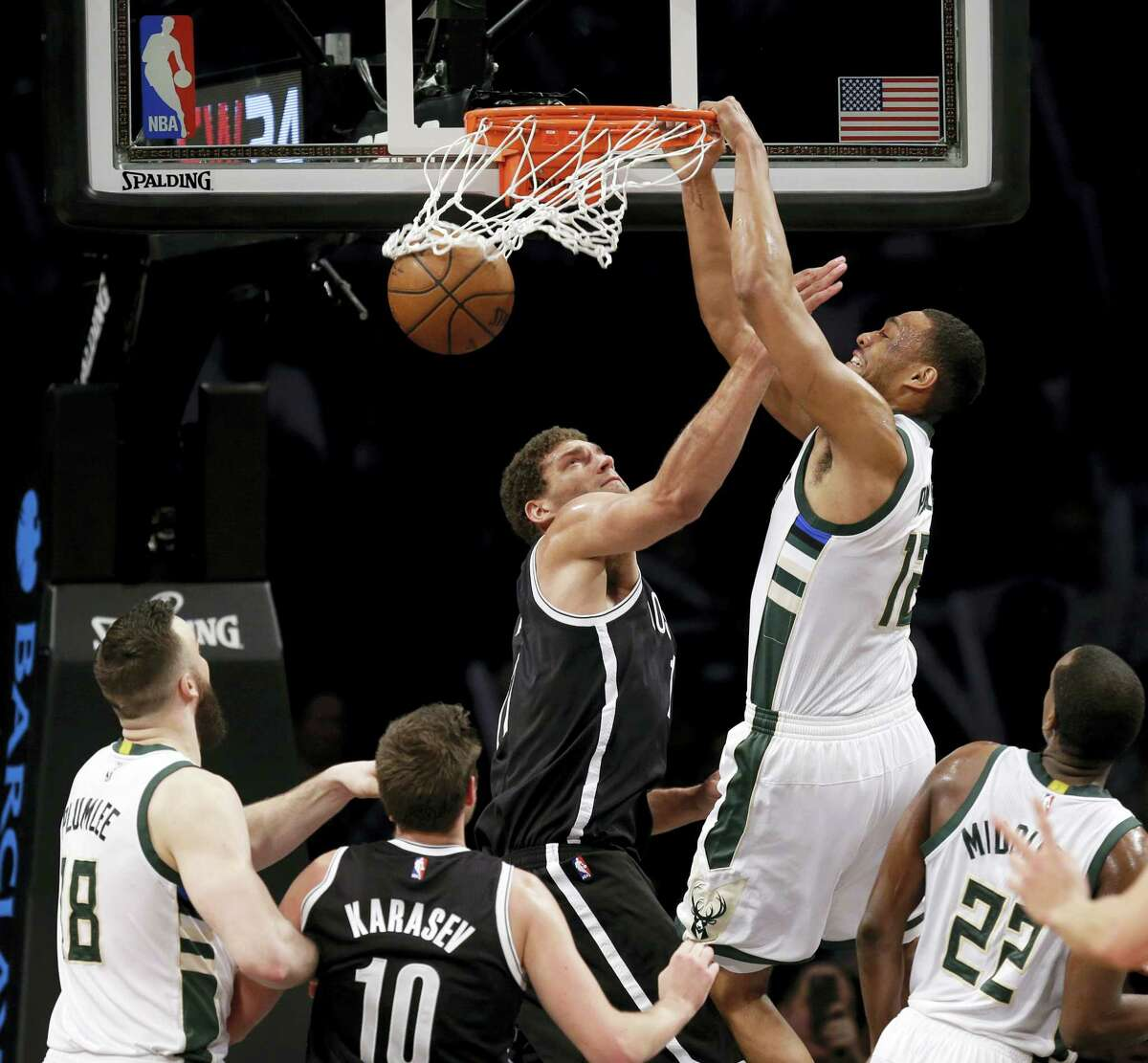 Milwaukee Bucks' Jabari Parker, second from right, dunks over Brooklyn Nets' Brook Lopez, third from left, during the second half of the NBA basketball game at the Barclays Center, Sunday, March 13, 2016 in New York. The Bucks defeated the Nets 109-100. (AP Photo/Seth Wenig)