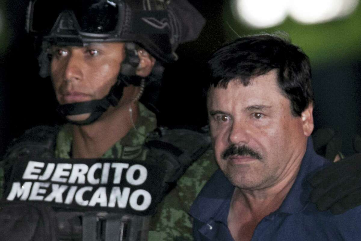"""Mexican drug lord Joaquin """"El Chapo"""" Guzman, right, is escorted by soldiers and marines to a waiting helicopter, at a federal hangar in Mexico City on Jan. 8, 2016. The world's most wanted drug lord was recaptured by Mexican marines Friday, six months after he fled through a tunnel from a maximum security prison in an escape that deeply embarrassed the government and strained ties with the United States."""