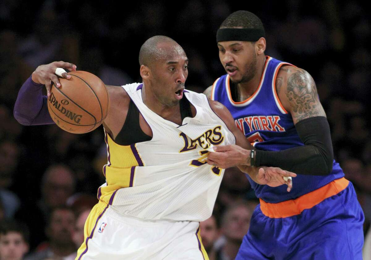 New York Knicks forward Carmelo Anthony, right, tugs on the jersey as Los Angeles Lakers forward Kobe Bryant, left, backs into him during the first half of an NBA basketball game in Los Angeles, Sunday, March 13, 2016. (AP Photo/Alex Gallardo)
