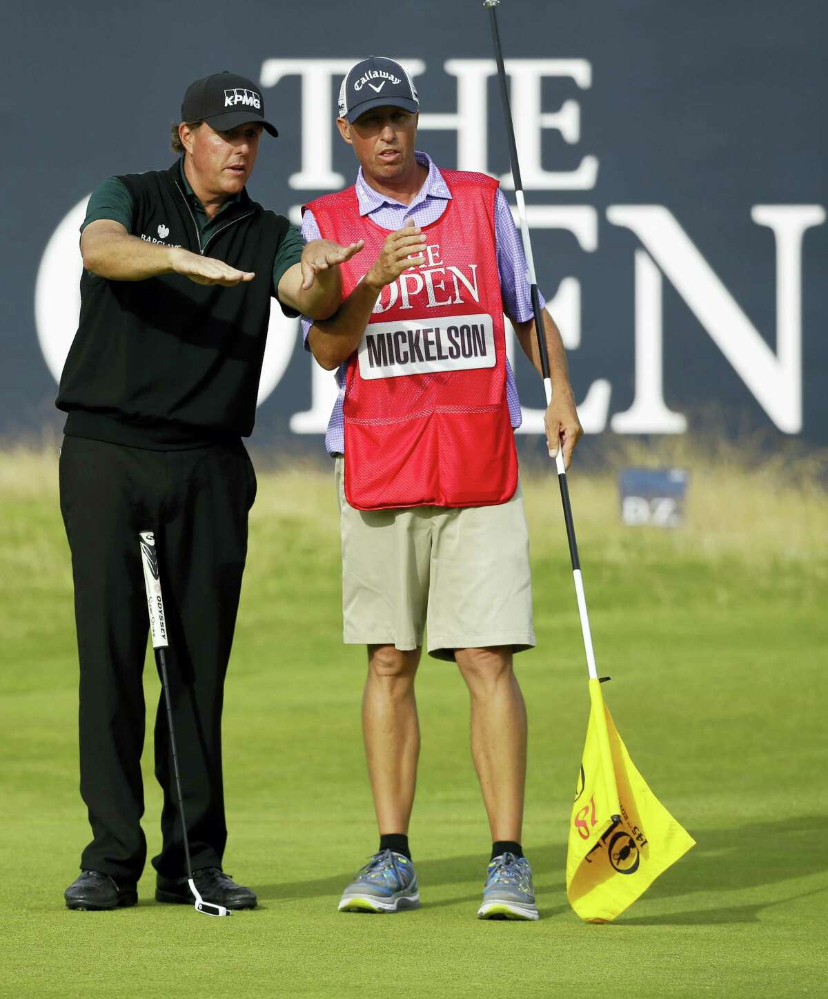 Phil Mickelson of the United States , left talks to his caddie Jim McKay on the 18th green as they look at his putt during the first round of the British Open Golf Championships at the Royal Troon Golf Club in Troon, Scotland, Thursday, July 14, 2016. (AP Photo/Matt Dunham)