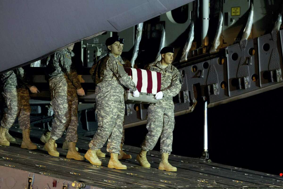 An Army team carries the transfer case containing the remains of Army Staff Sgt. Matthew Q. McClintock of Bernalillo, New Mexico, upon arrival at Dover Air Force Base, Delaware, on Friday. The Department of Defense announced the death of McClintock, who was supporting Operation Freedom's Sentinel in Afghanistan.