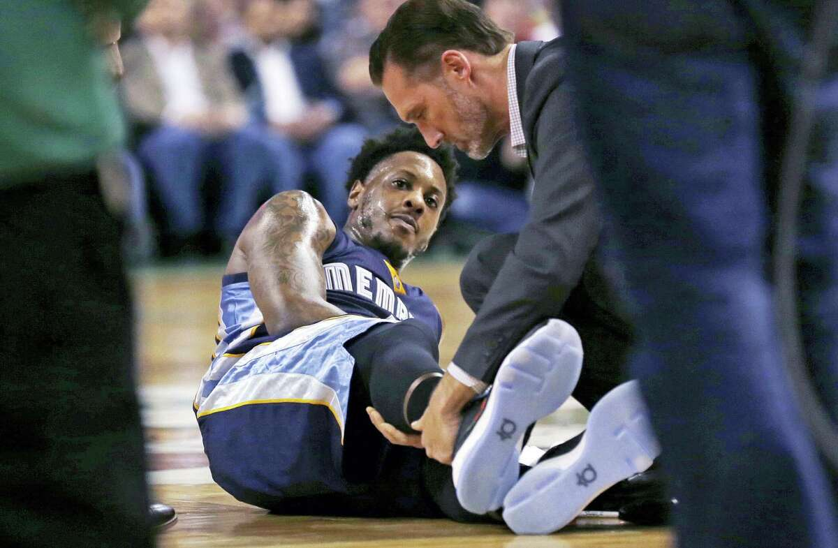 In this March 9, 2016 photo, Memphis Grizzlies guard Mario Chalmers lies on the court as he has his right leg examined during the team's NBA basketball game against the Boston Celtics in Boston. Chalmers is on target to be cleared for full basketball activity this week, eight months after rupturing his right Achilles. He thinks he could be on an NBA floor again by early December.
