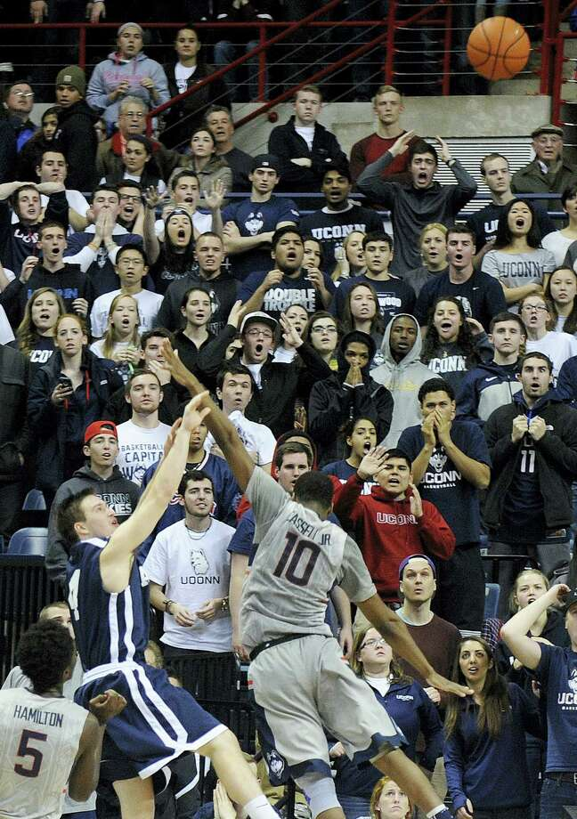 Yale's Jack Montague (4) shoots a game winning three-point shot while being guarded by Connecticut's Sam Cassell Jr. (10) during the second half of Yale's 45-44 upset victory in an NCAA college basketball game in Storrs, Conn., on Sunday, Dec. 5, 2014. Photo: AP Photo/Fred Beckham   / FR153656 AP