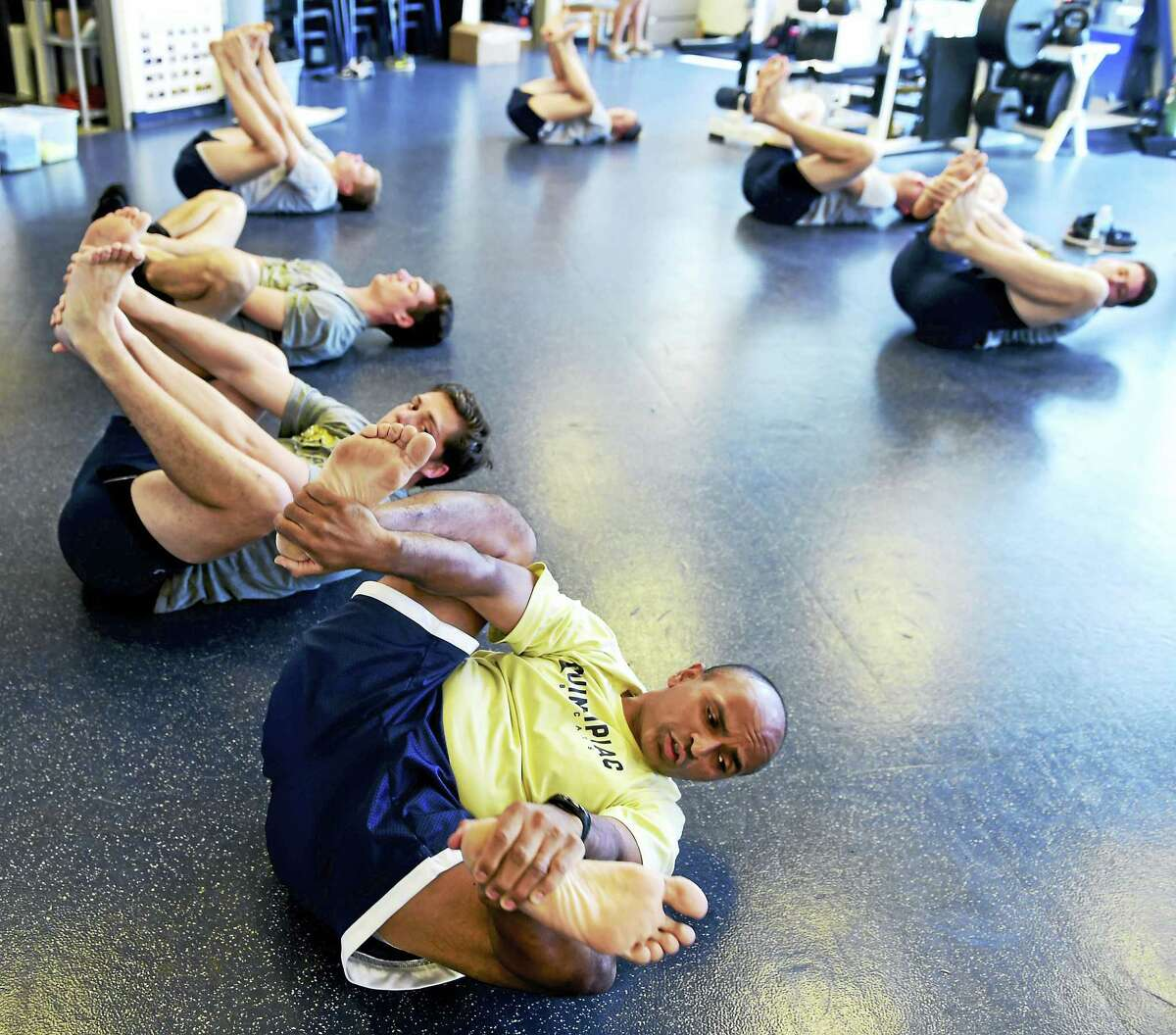 Brijesh Patel, bottom left, the Quinnipiac University strength and conditioning coach for winter sports, leads hockey players in a stretching and relaxation exercise on Wednesday.