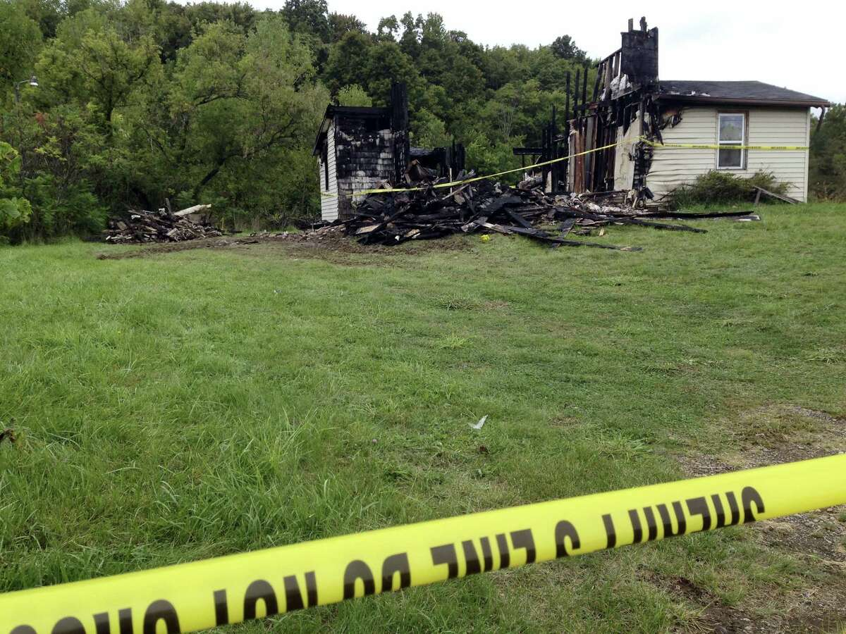Police tape cordons off the remains of a house. Wednesday, Sept. 14, 2016, in rural Richland County, near Mansfield, Ohio, where authorities say a woman's body was found nearby. Police say a suspect in the abduction of a woman in neighboring Ashland on Tuesday confessed to killing a woman in the house in June, which was then destroyed in a fire.