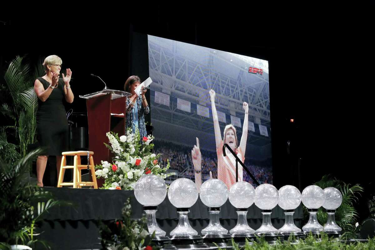 Tennessee women's basketball coach Holly Warlick, left, applauds during a video showing former Tennessee women's basketball coach Pat Summitt during a celebration of her life Thursday in Knoxville, Tenn.