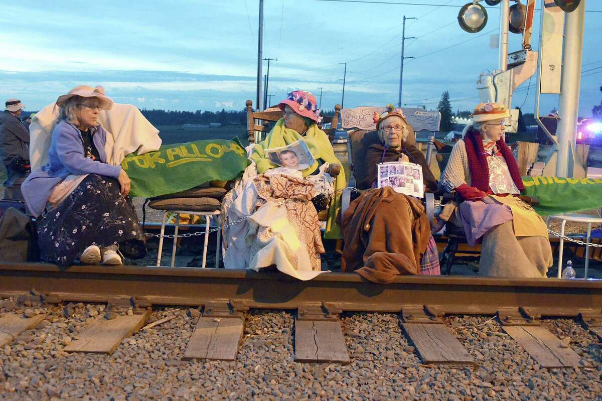 Members of the Seattle Raging Grannies sit in their rocking chairs chained together on the Burlington-Northern Railroad tracks at Farm to Market Road in Skagit County on May 13, 2016 in Burlington, Wash. From left are Deejay Sherman Peterson, Anne Thureson, Shirley Morrison and Rosy Betz-Zall.