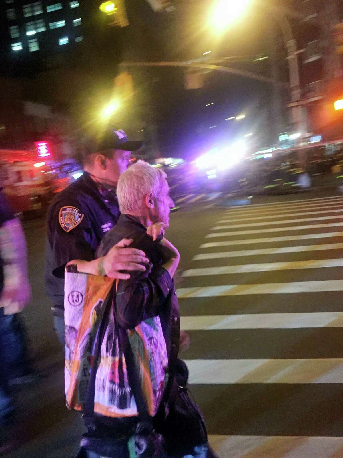 A police officer escorts an injured man away from the scene of a possible explosion on West 23rd Street in New York. Authorities said dozens suffered minor injuries.
