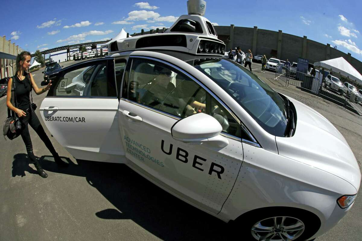 A journalist gets in a self driving Uber for a ride during a media preview at Uber's Advanced Technologies Center in Pittsburgh Monday. On Wednesday morning, dozens of self-driving Ford Fusions picked up riders who opted into a test program with Uber.