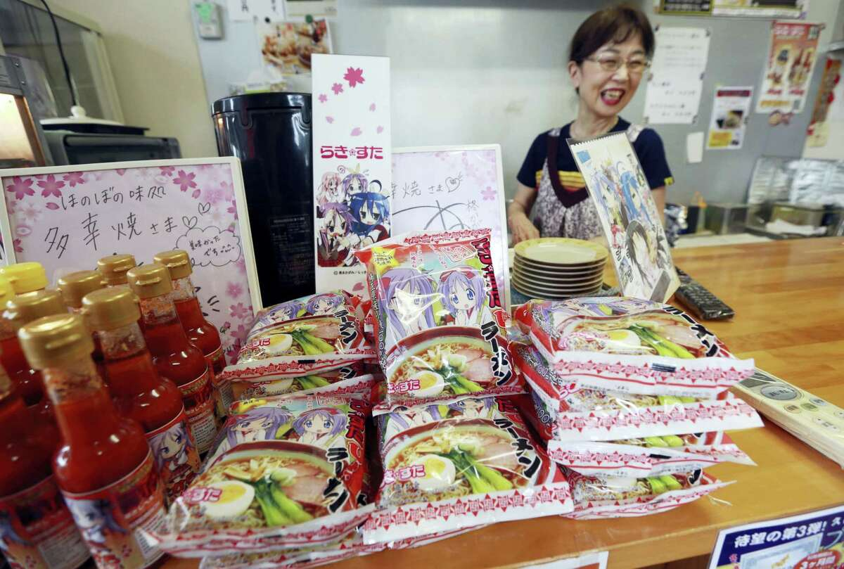 """Teruko Masaki, who runs an eatery, smiles behind a counter selling packs of ramen noodles and bottles of sauce, produced by the local chamber of commerce, featuring the characters of a popular TV animation series """"Lucky Star"""" or """"Raki Sta"""" at her restaurant near Washinomiya Jinja shrine in Kuki, Saitama prefecture, north of Tokyo."""