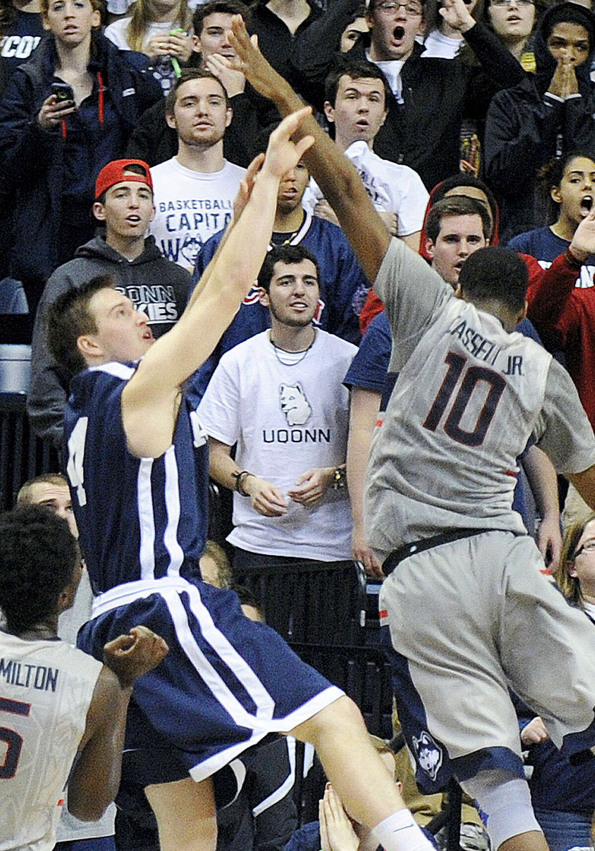 In this Dec. 5, 2014, photo, Yale's Jack Montague, left, shoots a game-winning three-point shot over Connecticut's Sam Cassell Jr. (10) during Yale's 45-44 upset victory in an NCAA college basketball game in Storrs.