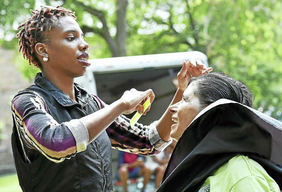 Hairdresser Patrice Johnson, of Hair's Kay Beauty Salon in New Haven, gives a free haircut to Donna Abate on the New Haven Green Wednesday.