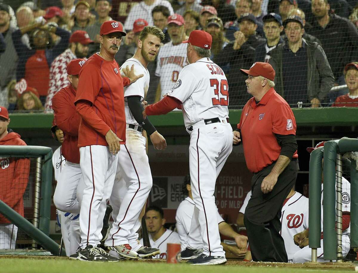 The Nationals' Bryce Harper, center, is restrained by pitching coach Mike Maddux, left, and hitting coach Rick Schu (39) after Harper was ejected in the dugout during the ninth inning of a game against the Tigers on May 9.