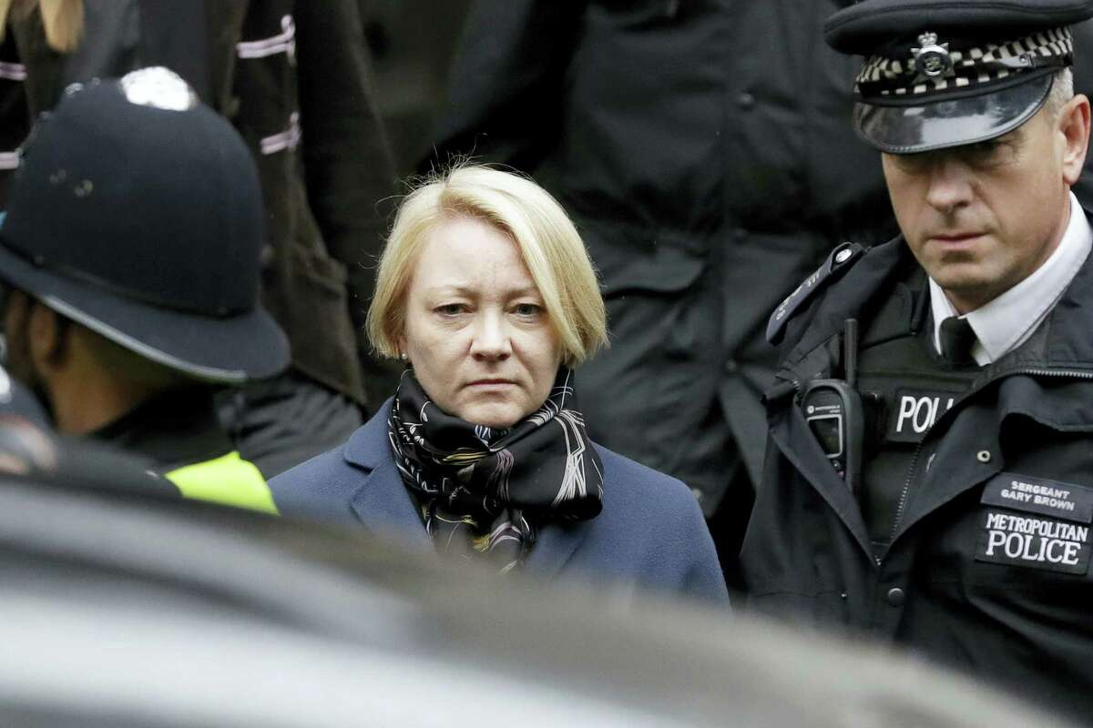 Swedish prosecutor Ingrid Isgren walks to a vehicle flanked by British police officers as she leaves the entrance of the Ecuadorian embassy in London on Monday, Nov. 14, 2016. Isgren arrived at the embassy Monday to question Wikileaks founder Julian Assange about allegations concerning possible sexual misconduct committed in Sweden six years ago.